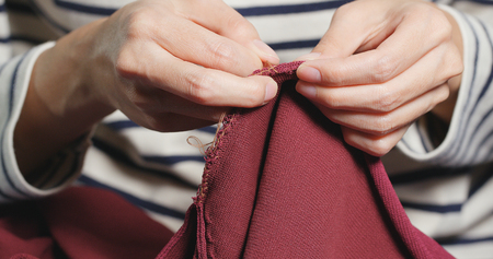 Woman Sews with a needle and thread Stock Photo