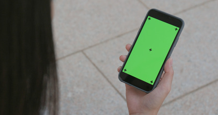 Woman holding cellphone with green screen