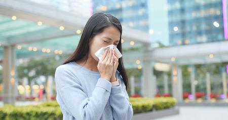 Woman sneeze at outdoor city Standard-Bild