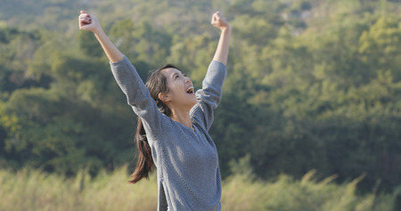 Excited woman raising hand up