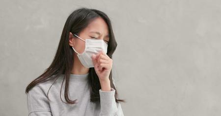 Vrouw die masker draagt en zich ziek voelt