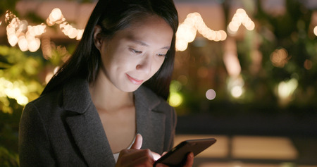 Woman use of cellphone for online at outdoor in the evening