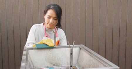 Woman Scouring barbecue oven with Scour Pad