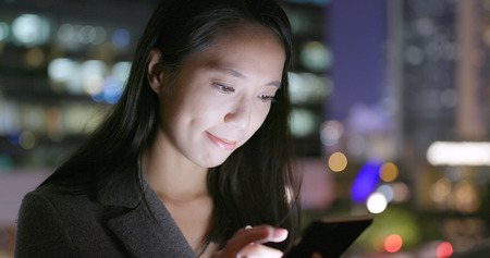 Business woman sending sms on cellphone in city at night