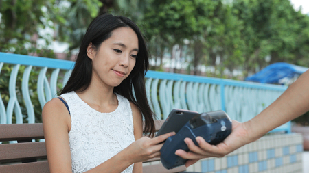 Woman using mobile phone for payment 写真素材