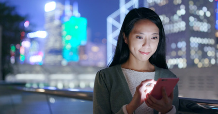 Woman looking at smart phone in city at night Standard-Bild