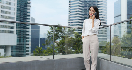 Businesswoman talk to mobile phone in city