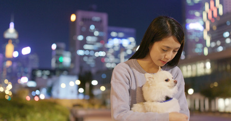 Woman hugging with her pomeranian dog in city at night
