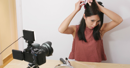 Woman taking video of making hair for posting online