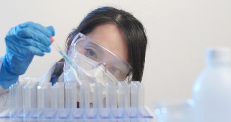 Chemist holding a test tube with liquid