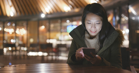 Young Woman using mobile phone at night Banco de Imagens