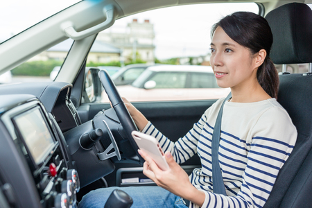 Woman driving car and using cellphone