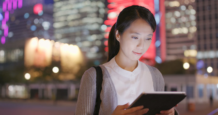 Business woman use of tablet computer at night in the outdoor station Stockfoto