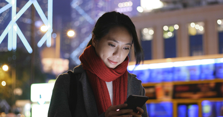 Woman look at smart phone in city