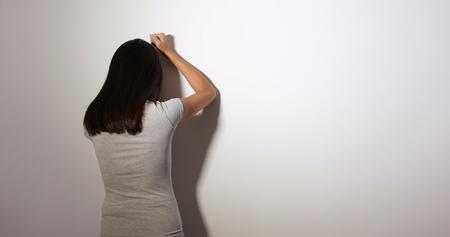 Upset woman facing the wall and crying