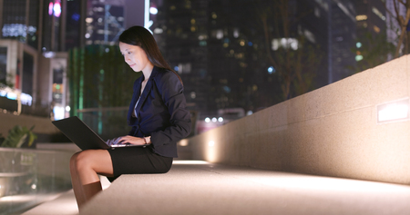 Business woman work on notebook computer in city at night