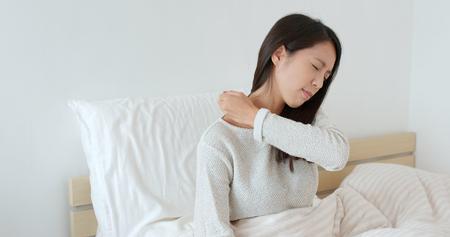 Frau, die Schulterschmerzen auf Bett fühlt