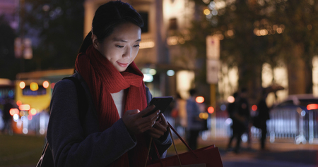 Young Woman use of smart phone in city at night