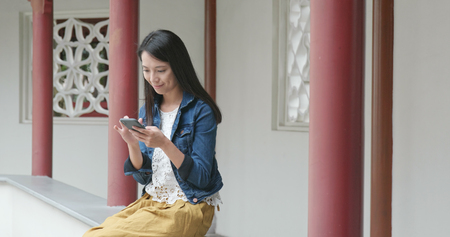 Woman use of mobile phone in Chinese garden Banque d'images - 116057835