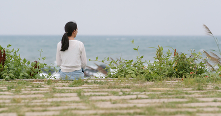 Back view of woman sit down and look at the sea