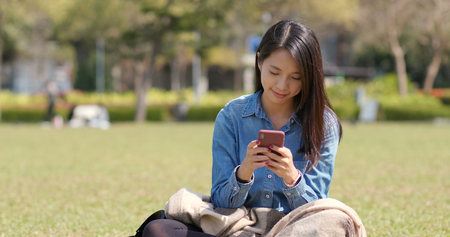 Young woman use of mobile phone and sitting on green lawn