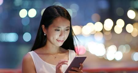 Woman look at smart phone at night