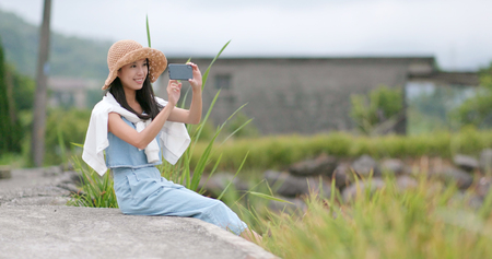 Travel woman taking photo in the nature landscape