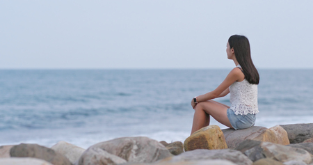 Woman sitting at the seaside and look far away 写真素材