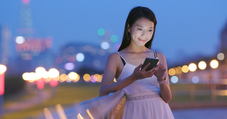 Asian woman use of cellphone at night