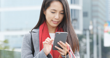 Young woman using mobile phone and holding shopping bag Stock Photo