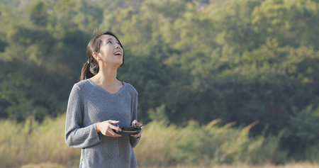 Woman controling flying drone in the park Stock Photo