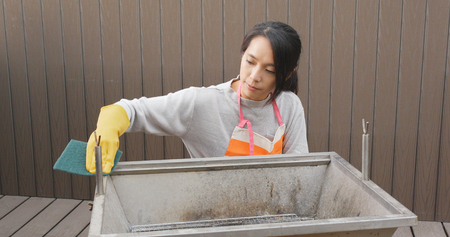 Woman cleaning of barbecue oven