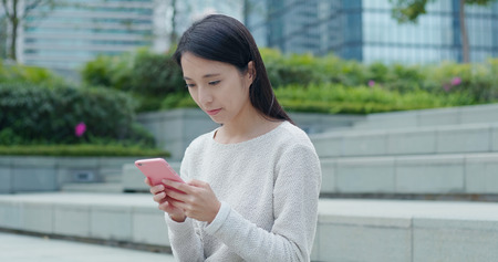 Woman using cellphone at outdoor Imagens