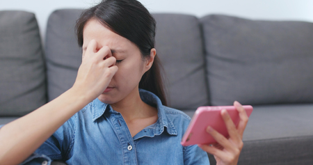 Woman watching on cellphone and feeling eye pain at home 版權商用圖片 - 117283936