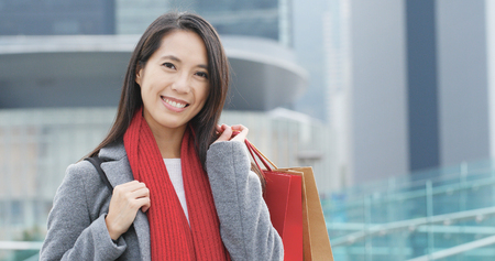 Happy woman holding shopping bag at outdoor Stock Photo