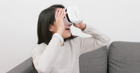 Woman watching with VR device at home Banco de Imagens