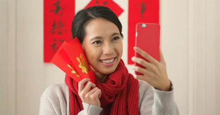 Chinese woman taking selfie and holding with red packet in lunar new year holiday