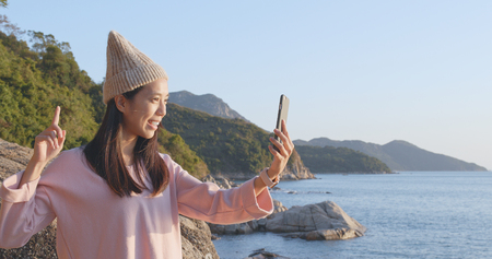 Woman taking selfie via cellphone with the sea background