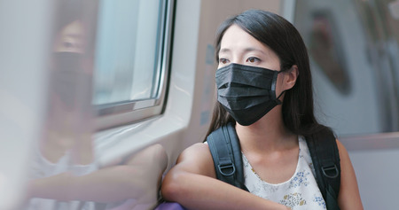 Woman wearing protective mask and taking train