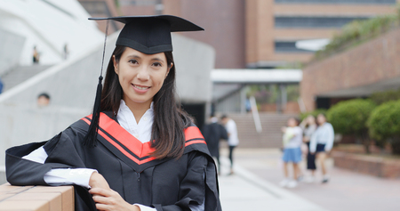 Woman wearing graduation gown in campus