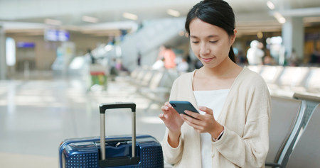 Woman use of mobile phone in the airport Stock Photo