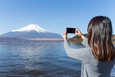 Woman take photo by mobile phone of Mount Fuji Stockfoto