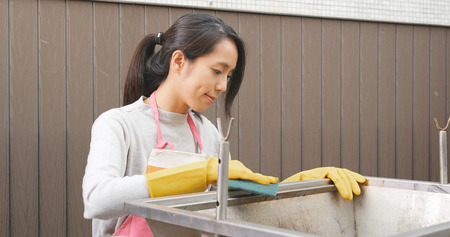 Woman cleaning of barbecue oven at outdoor with Scour Pad