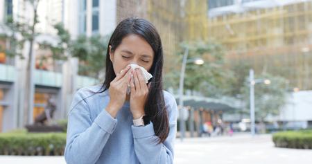 Woman sneezing at outdoor 免版税图像