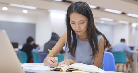 Woman writing on note in university library