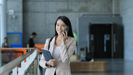 Business woman holding tablet computer and talk to mobile phone