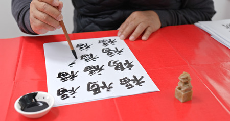 Man write chinese calligraphy for lunar new year, words mean luck