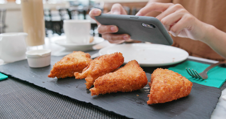 Woman taking photo on fried chicken wing 스톡 콘텐츠