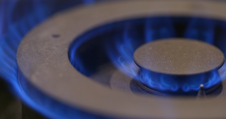 Stove burner igniting into a blue cooking flame