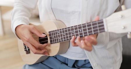Woman playing ukulele at home